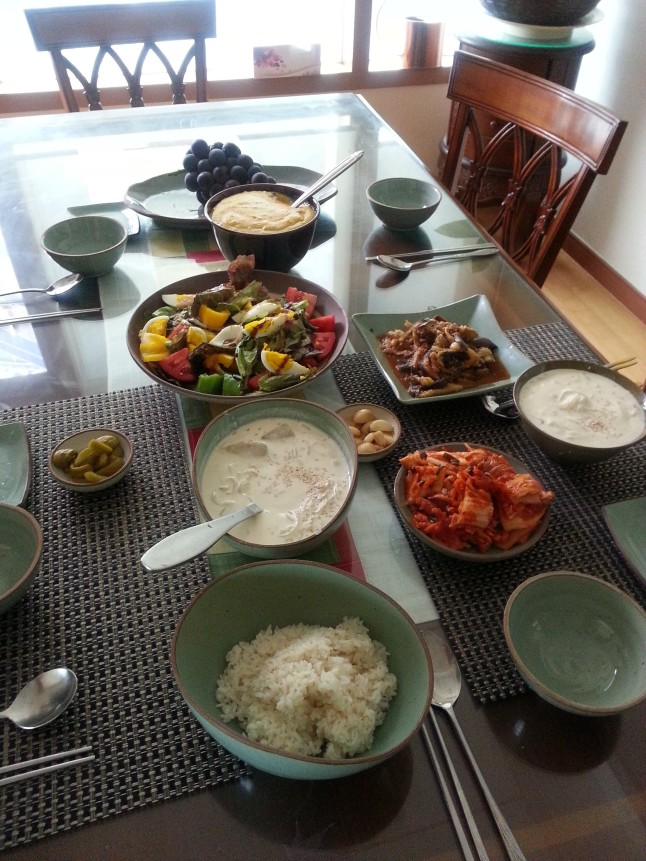 A healthy filling vegetarian Korean breakfast that includes salad, pumpkin porridge, cold Korean Soybean Noodle Soup (Kong Gooksu), rice,  kimchi, fermented eggplants, pickled green plum, garlic and grapes.