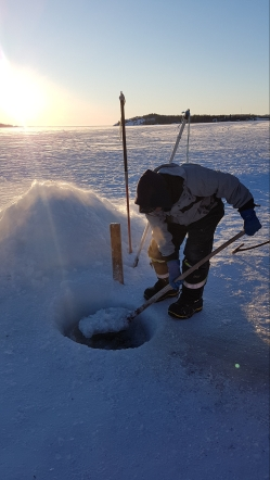 Our guide, William, demonstrating how to make a hole for ice fishing.
